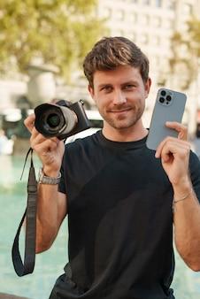 Uśmiechnięty mężczyzna pokazujący aparat fotograficzny i smartfon na placu miejskim