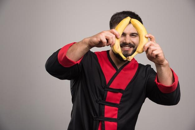 Uśmiechnięty mężczyzna pokazujący dwa banany na ciemnej powierzchni.