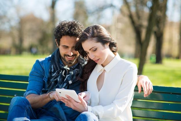 Uśmiechnięty mężczyzna pokazuje jego pastylkę dziewczyna w parku