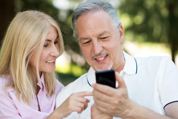 Uśmiechnięty mężczyzna pokazuje jego telefon komórkowego jego żona