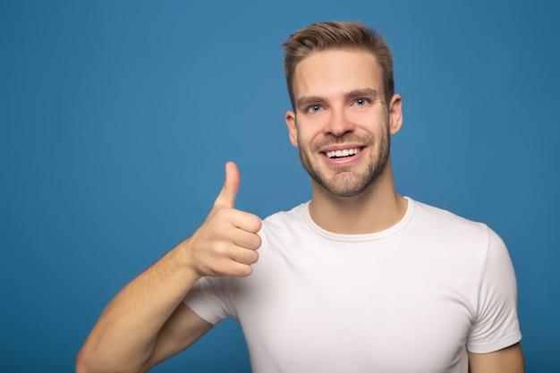 Uśmiechnięty mężczyzna pokazuje kciuk up odizolowywającego na błękicie