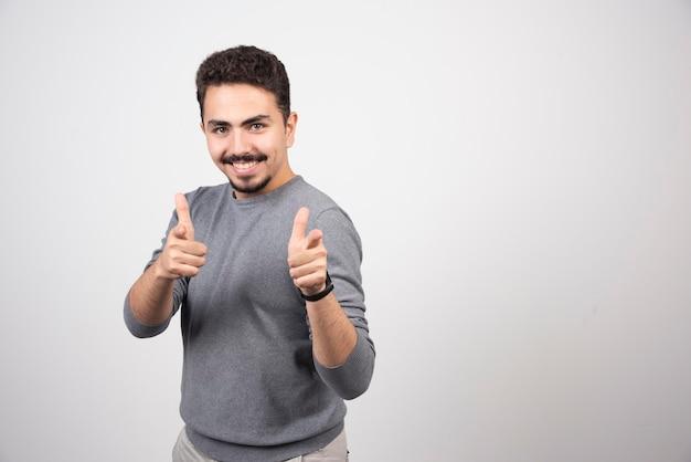 Uśmiechnięty mężczyzna pokazuje kciuki i patrząc na kamery.