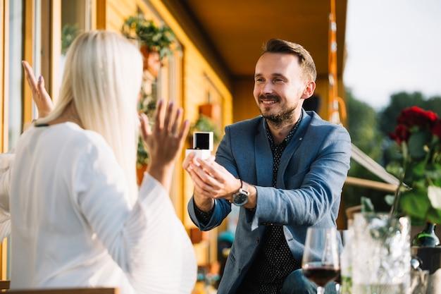 Uśmiechnięty mężczyzna pokazuje pierścionek zaręczynowego jej dziewczyna