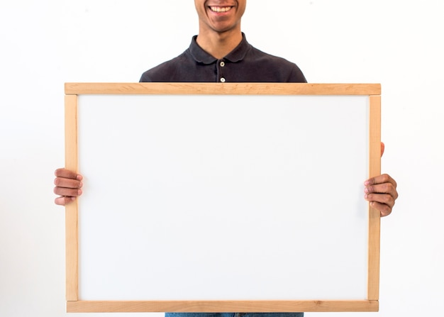 Uśmiechnięty mężczyzna pokazuje puste miejsce pustą białą deskę