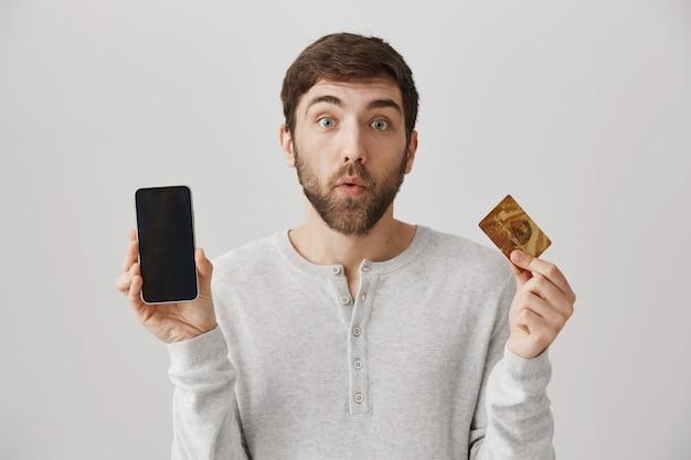 Uśmiechnięty mężczyzna pokazuje wyświetlacz smartfona i kartę kredytową. zakupy internetowe