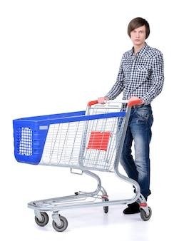 Uśmiechnięty mężczyzna pozuje obok pustego wózek na zakupy.