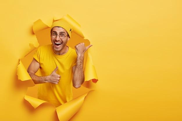 Uśmiechnięty mężczyzna pozuje przez podarty papier