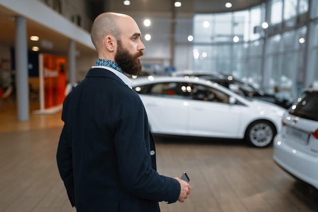 Uśmiechnięty mężczyzna pozuje w salonie samochodowym. klient w salonie nowych pojazdów, mężczyzna kupujący samochód, dealer samochodowy