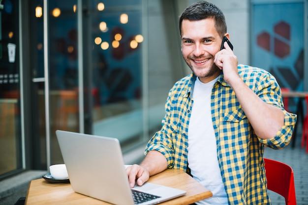 Uśmiechnięty mężczyzna pozuje z gadżetami w kawiarni