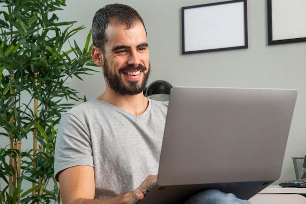 Uśmiechnięty mężczyzna pracujący w domu na laptopie