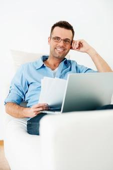 Uśmiechnięty mężczyzna pracujący w domu