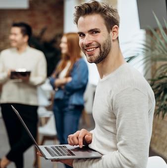 Uśmiechnięty mężczyzna pracuje na laptopie stojąc