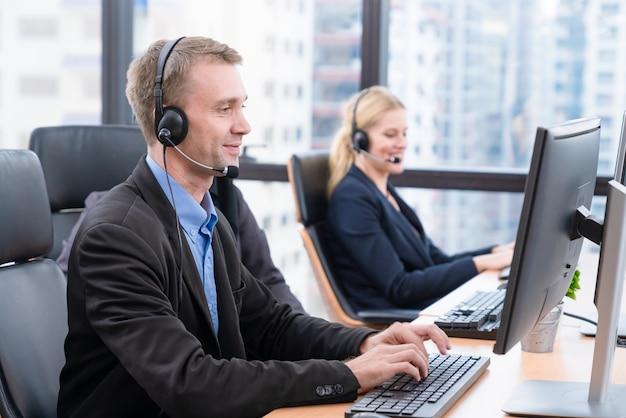 Uśmiechnięty mężczyzna pracuje opieki obsługi klienta jest ubranym hełmofon