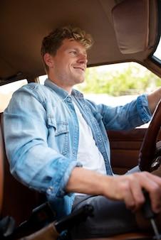 Uśmiechnięty mężczyzna prowadzący samochód średni strzał