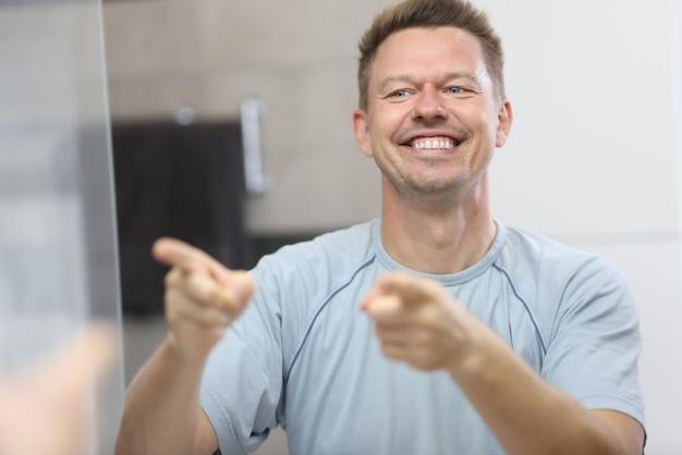 Uśmiechnięty mężczyzna przed lustrem wskazuje na swoje odbicie.