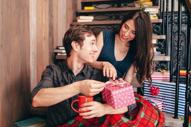 Uśmiechnięty mężczyzna przedstawia prezent na boże narodzenie szczęśliwej kobiety.