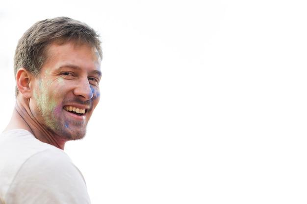 Uśmiechnięty mężczyzna przy holi z farbą na jego twarzy