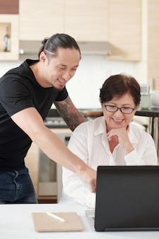 Uśmiechnięty mężczyzna rasy mieszanej wyjaśnia matce, jak korzystać z nowego laptopa i znaleźć przydatne informacje w internecie