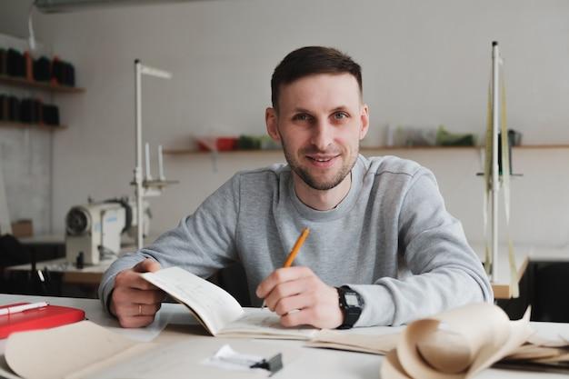 Uśmiechnięty mężczyzna robi inżynierii lub zarządza pracą przy ogólnym warsztacie.