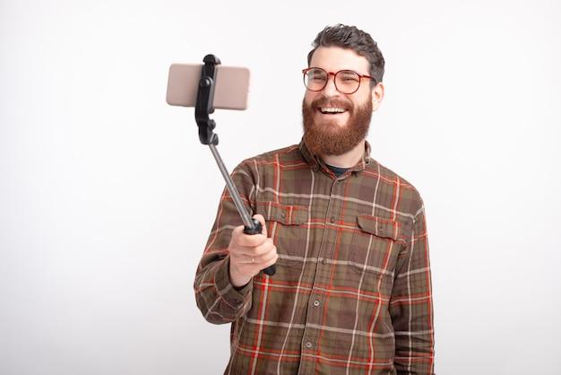 Uśmiechnięty mężczyzna robi selfie na białym tle.