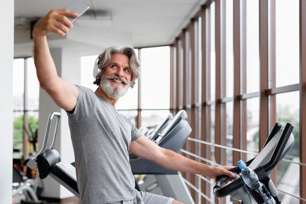 Uśmiechnięty mężczyzna robi selfie na siłowni