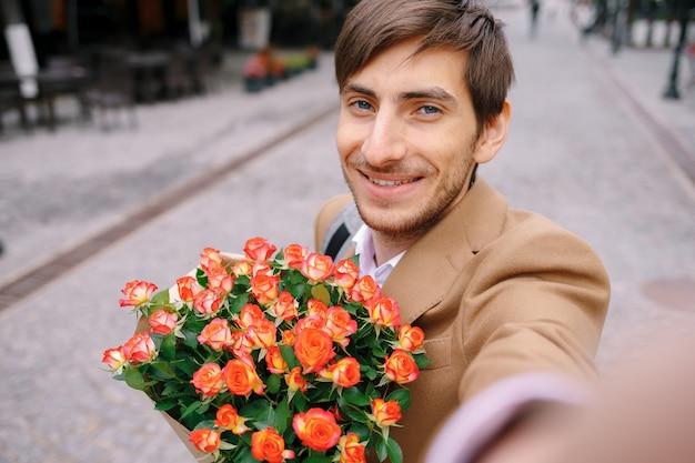 Uśmiechnięty mężczyzna robi selfie z kwiatami