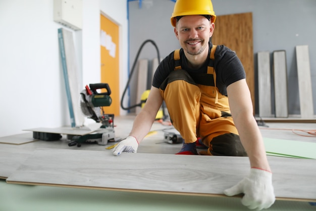 Uśmiechnięty mężczyzna robotnik budowlany układa nową wykładzinę podłogową