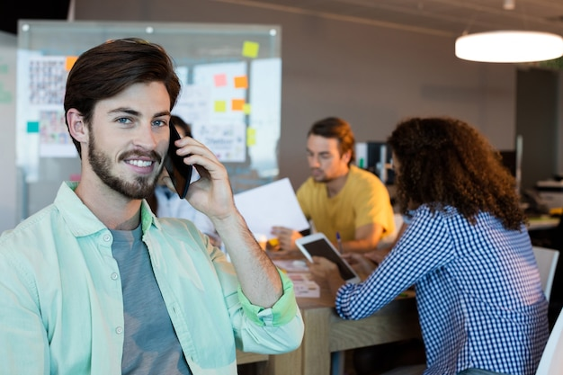 Uśmiechnięty mężczyzna rozmawia przez telefon komórkowy w biurze