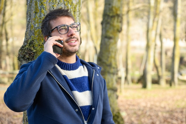 Uśmiechnięty mężczyzna, rozmawia przez telefon komórkowy w parku jesień.