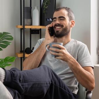 Uśmiechnięty mężczyzna rozmawia przez telefon mając kawę w domu