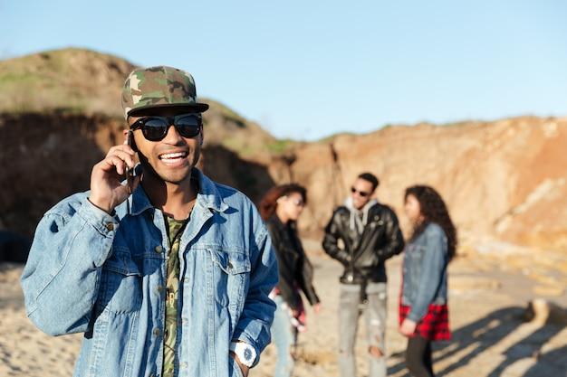 Uśmiechnięty mężczyzna rozmawia przez telefon spaceru na plaży z przyjaciółmi