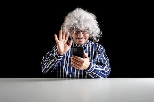 Uśmiechnięty mężczyzna siedzący przy biurku i rozmawiający na czacie wideo na smartfonie na czarnym tle