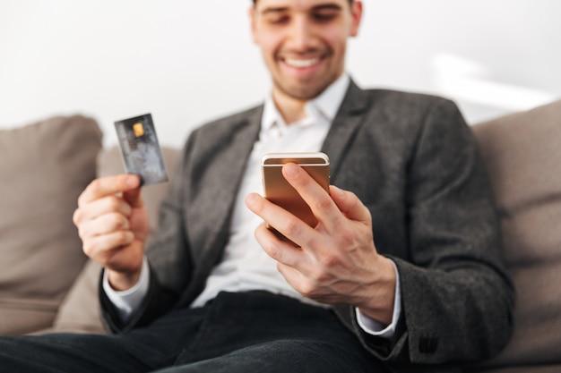 Uśmiechnięty mężczyzna siedzi na kanapie z kartą kredytową w domu
