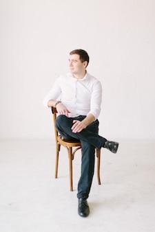 Uśmiechnięty mężczyzna siedzi na krześle