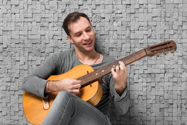 Uśmiechnięty mężczyzna siedzi na podłodze i gra