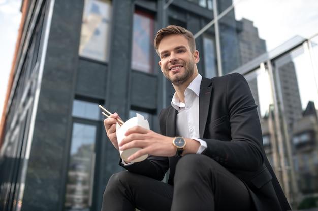 Uśmiechnięty mężczyzna siedzi na schodach i je azjatyckie jedzenie