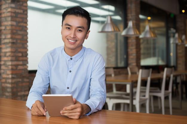 Uśmiechnięty mężczyzna siedzi na tabeli z komputera typu tablet cafe