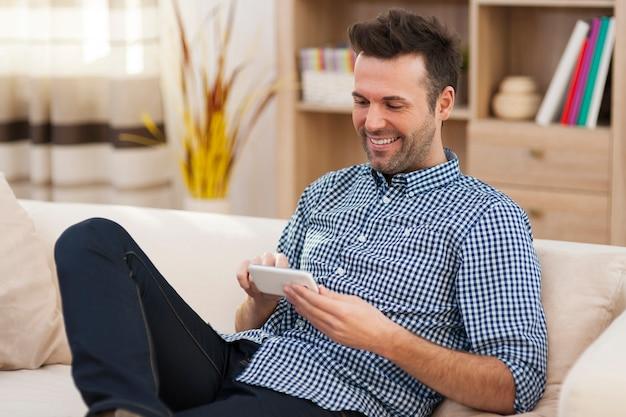 Uśmiechnięty mężczyzna siedzi na trenerze i za pomocą inteligentnego telefonu