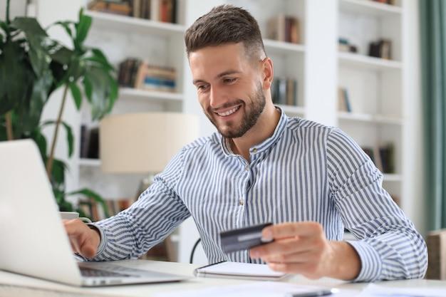 Uśmiechnięty mężczyzna siedzi w biurze i płaci kartą kredytową ze swoim laptopem.