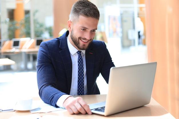 Uśmiechnięty mężczyzna siedzi w biurze i za pomocą swojego laptopa.