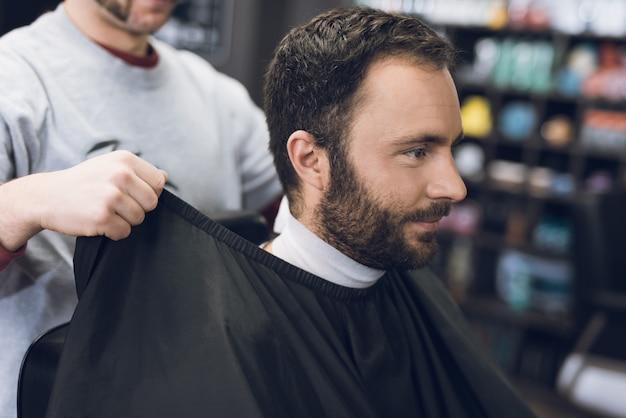 Uśmiechnięty mężczyzna siedzi w salonie fryzjerskim