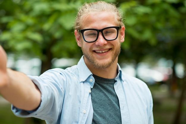 Uśmiechnięty mężczyzna sięgający ręką do pozowania