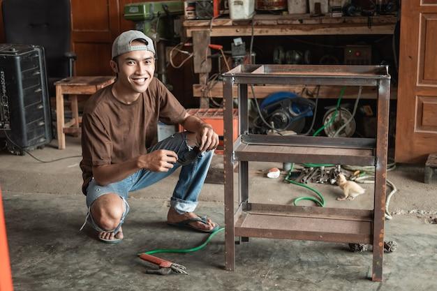 Uśmiechnięty mężczyzna spawacz w kucki po użyciu spawania elektrycznego do spawania metalowej ramy na tle warsztatu spawalniczego