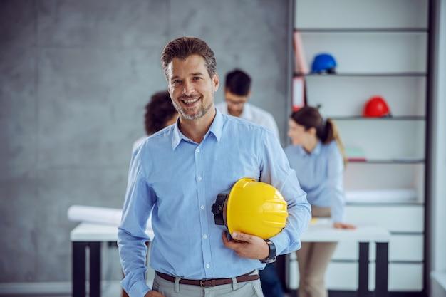 Uśmiechnięty mężczyzna starszy architekt trzymając kask w ręce, stojąc w biurze.