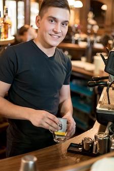 Uśmiechnięty mężczyzna stawia herbacianych batów w filiżankę