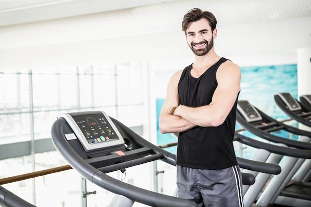 Uśmiechnięty mężczyzna stojący na bieżni z rękami skrzyżowanymi na siłowni