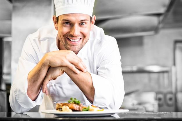 Uśmiechnięty mężczyzna szef kuchni z gotowanym jedzeniem w kuchni