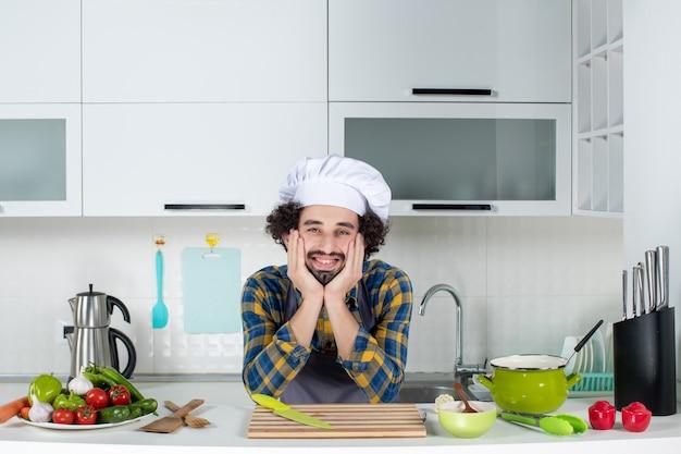 Uśmiechnięty mężczyzna szef kuchni ze świeżymi warzywami pozuje w białej kuchni