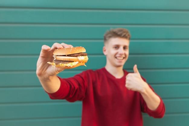 Uśmiechnięty mężczyzna trzyma apetyczny burger w dłoniach i pokazuje kciuki do góry.