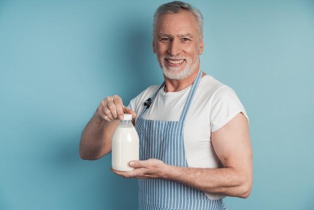 Uśmiechnięty mężczyzna trzyma butelkę mleka
